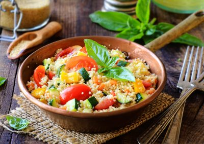 Delicious homemade vegetarian couscous with tomatoes, carrots, zucchini, yellow bell pepper and fresh basil on a dark rustic wooden kitchen table